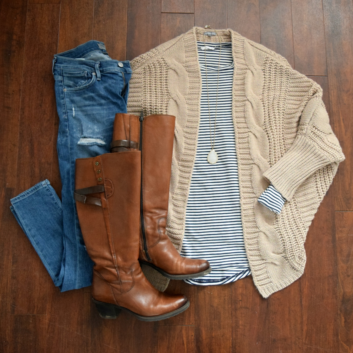 A cozy cardigan, striped tee, high-waisted jeans, and riding boots