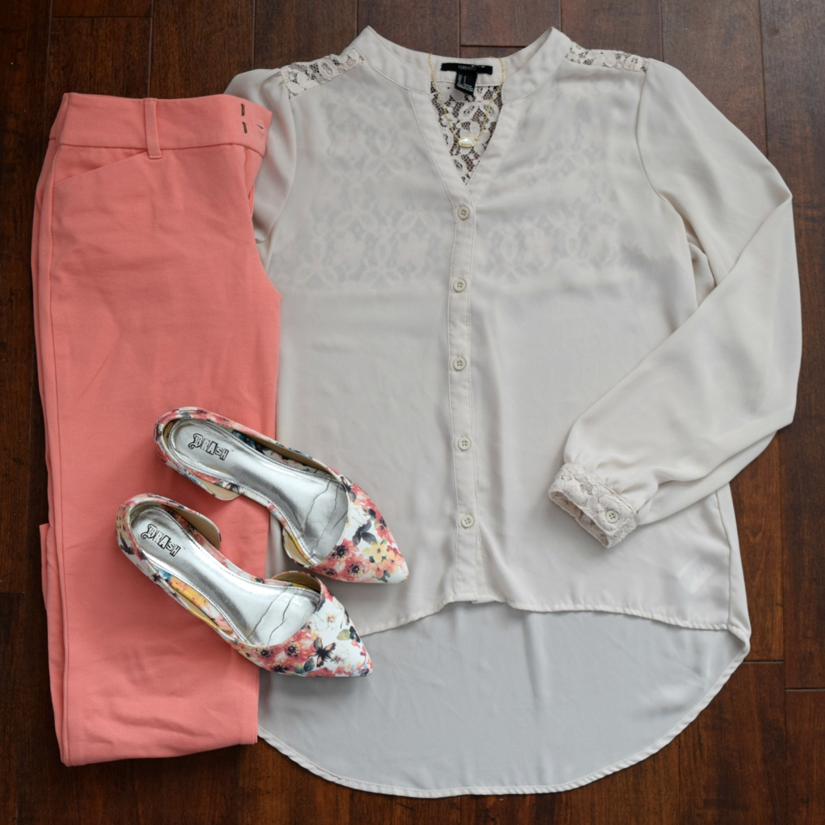 pastel pants, a silky ivory blouse, and floral flats